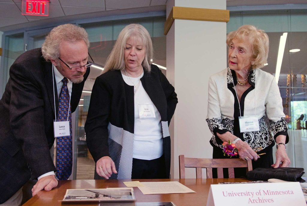 Maxine Wallin, right, browses through historical materials at the opening of the Maxine Houghton Wallin Special Collections Research Center on May 13, 2018. With her are her son Lance and Kris Kiesling, Director of the Libraries Archives and Special Collections.